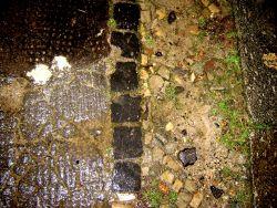 Berlijns trottoir bij avond, let op het antislip ''pukkeltjesasfalt'' links, dat gemaakt wordt door er een soort mat op te leggen voor het droogt. je ziet het in Frankrijk ook. een motief dat verwant is met de afdrukken van planken bekisting in beton.